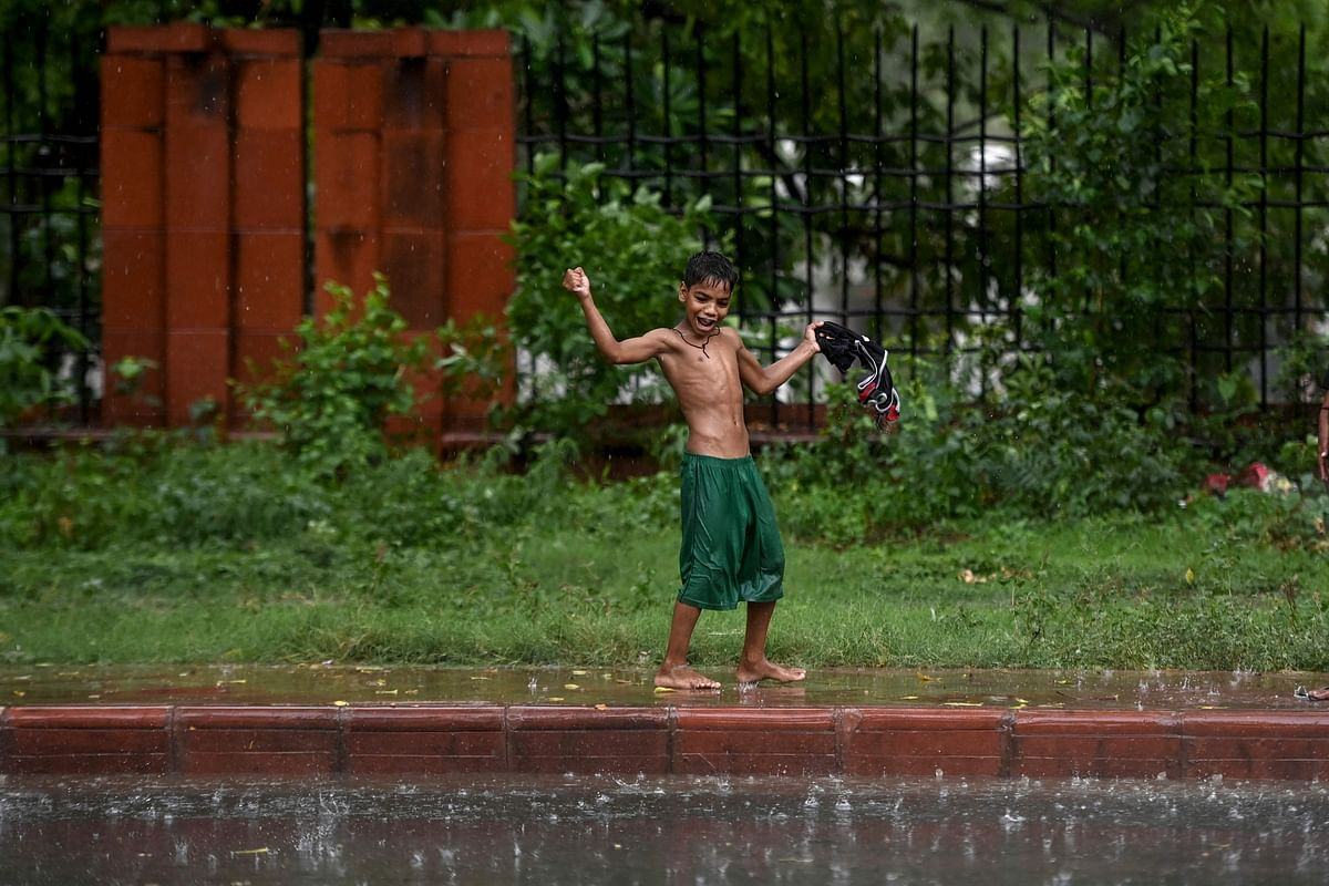 A boy plays along a footpath during a monsoon rainfall in New Delhi on June 17, 2021.