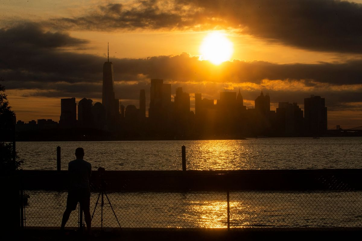 The New York skyline is seen as the Moon partially covers the sun during a partial solar eclipse on June 10, 2021 seen from Jersey City, New Jersey.