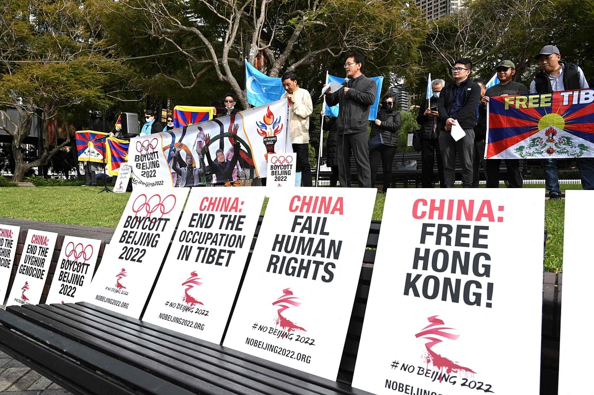 Protesters hold up placards and banners as they attend a demonstration in Sydney on June 23, 2021 to call on the Australian government to boycott the 2022 Beijing Winter Olympics over Chinas human rights record.