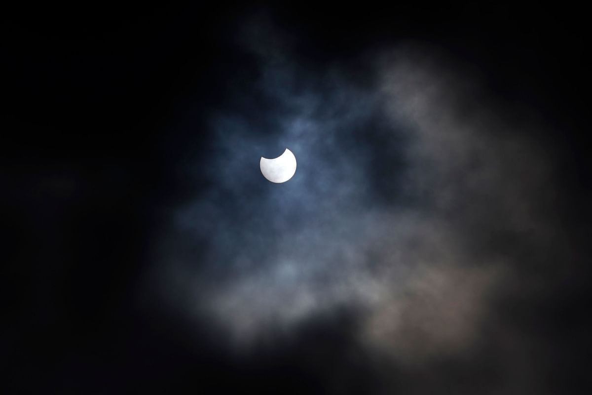 A partial solar eclipse is seen through cloud cover from Primrose Hill in central London on June 10, 2021.