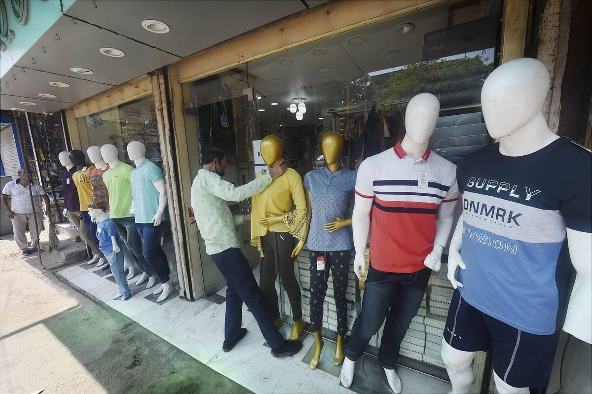 A worker arranges mannequins outside a shop