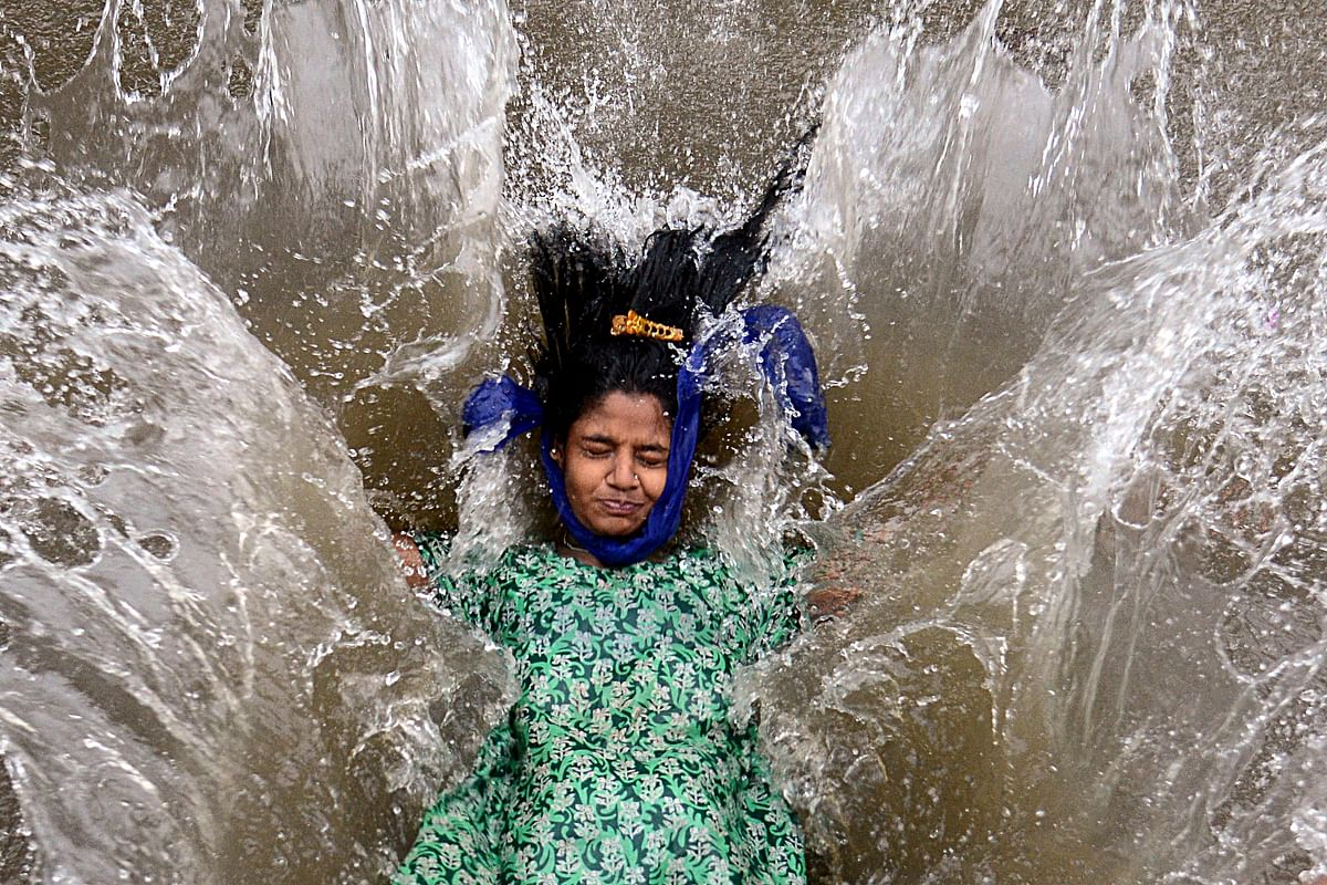 A girl plays in a waterlogged street following a heavy monsoon rainfall in Mumbai on June 9, 2021.