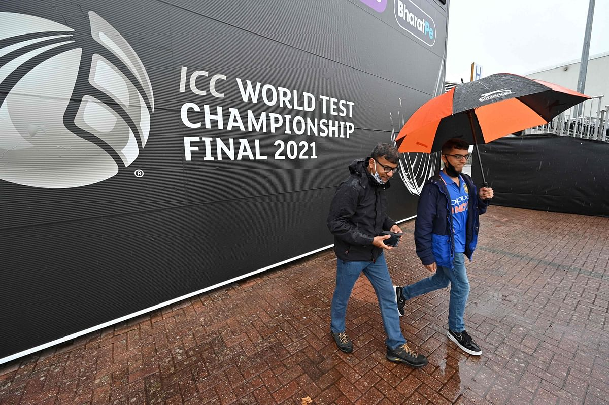 Indian fans walk in the rain on the fourth day of the ICC World Test Championship Final between New Zealand and India at the Ageas Bowl in Southampton, southwest England on June 21, 2021.