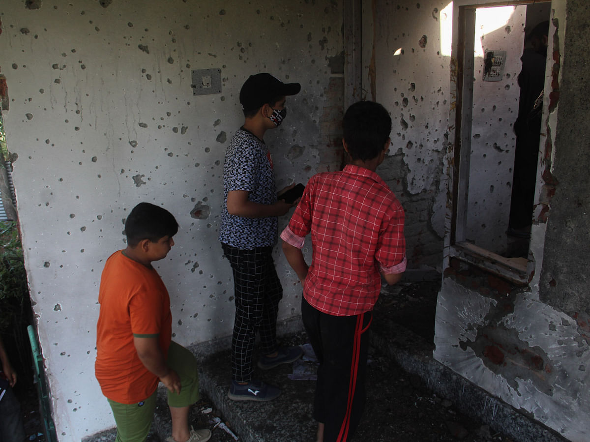 Kashmiri children's stands next to the bullet-ridden wall inside the house that was damaged during a gunfight between security forces and militants in Maloora locality on the outskirts of Srinagar, Jammu & Kashmir.
