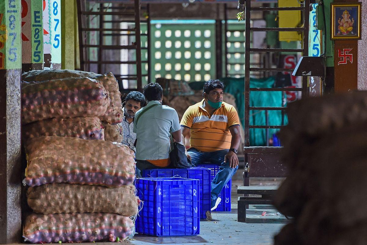 Vendors sit inside a storage area of a vegetable wholesale market in Navi Mumbai on June 15, 2021.
