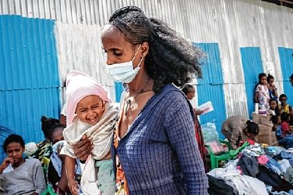 An internal displaced mother, who fled the violence in Ethiopia's Tigray region, carries her child in Mekele, the Tigray capital.