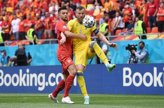 Ukraine (R) and North Macedonia players in mid field action