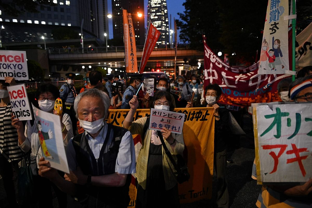 A group of anti-Olympic activists march from the metropolitan government building as they protest to mark the 30 days before the Olympic Games opening ceremonies, in Tokyo on June 23, 2021.