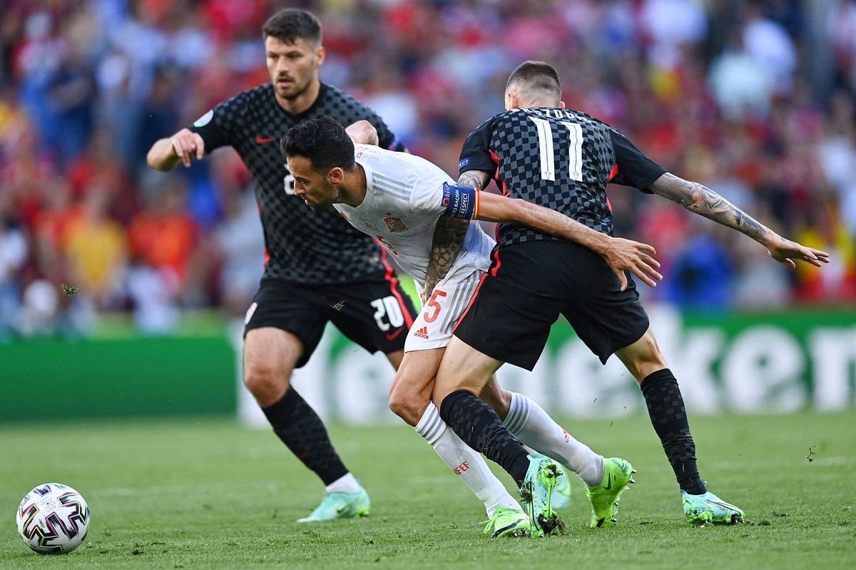 Spain's midfielder Sergio Busquets (C) challenges Croatia's midfielder Marcelo Brozovic (R) and Croatia's forward Bruno Petkovic