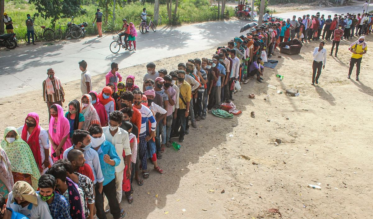 Beneficiaries not adhering to social distancing norms, wait in queues to receive COVID-19 vaccine dose, at a government school at Fazilpur village in Gurugram, Wednesday, June 30, 2021.