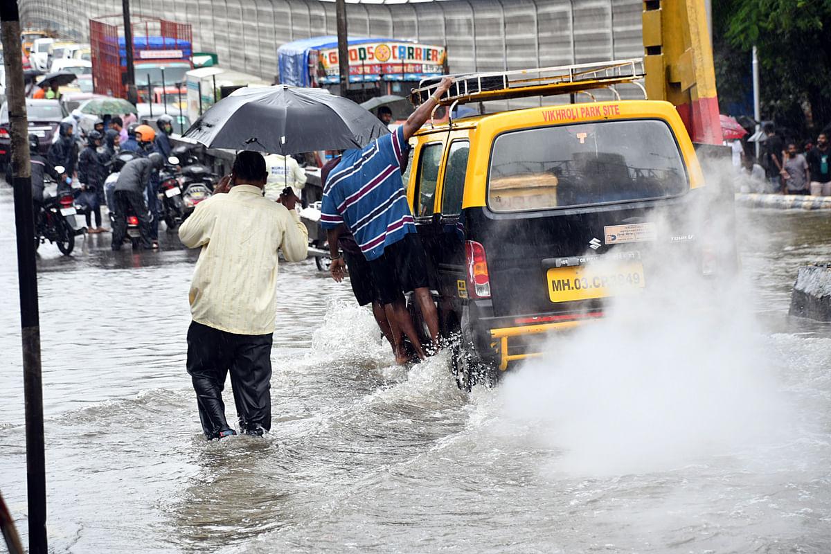 Maharashtra, June 12 (ANI): People commute through waterlogged roads during heavy rainfall in Mumbai on Saturday.
