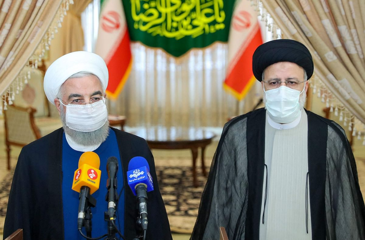 A handout picture provided by the Iranian presidency on June 19, 2021, shows outgoing President Hassan Rouhani (L) taking in part in a press conference with President-elect Ebrahim Raisi (R).