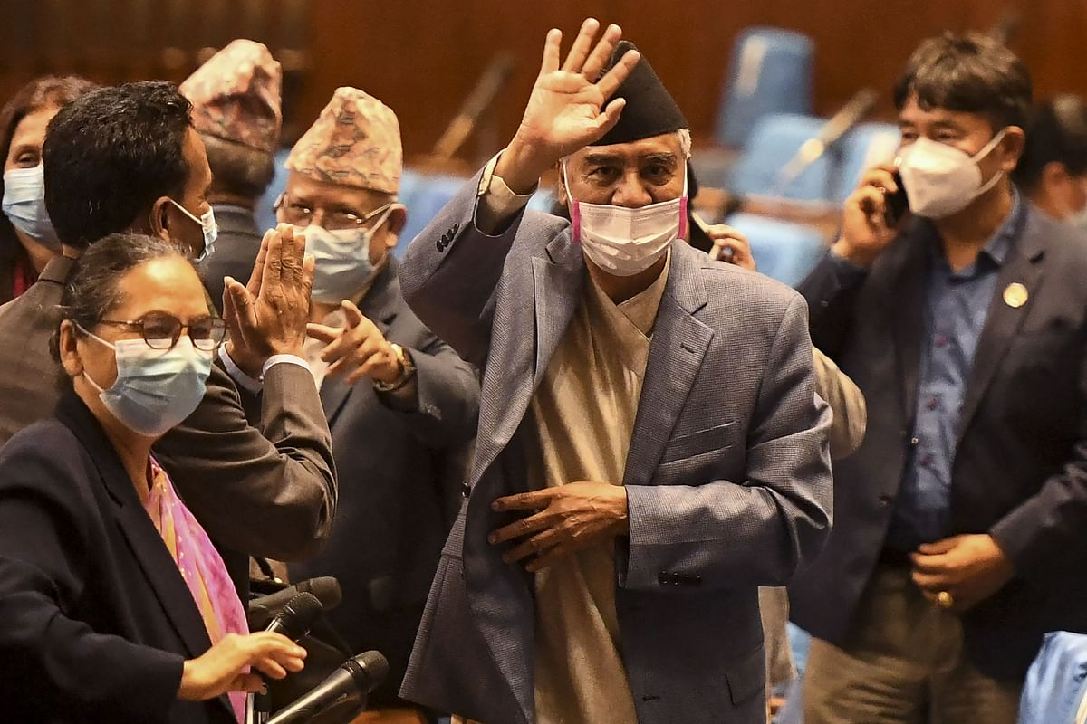 Nepal's newly appointed PM Sher Bahadur Deuba (C) wave to journalists after winning a vote of confidence in Kathmandu.