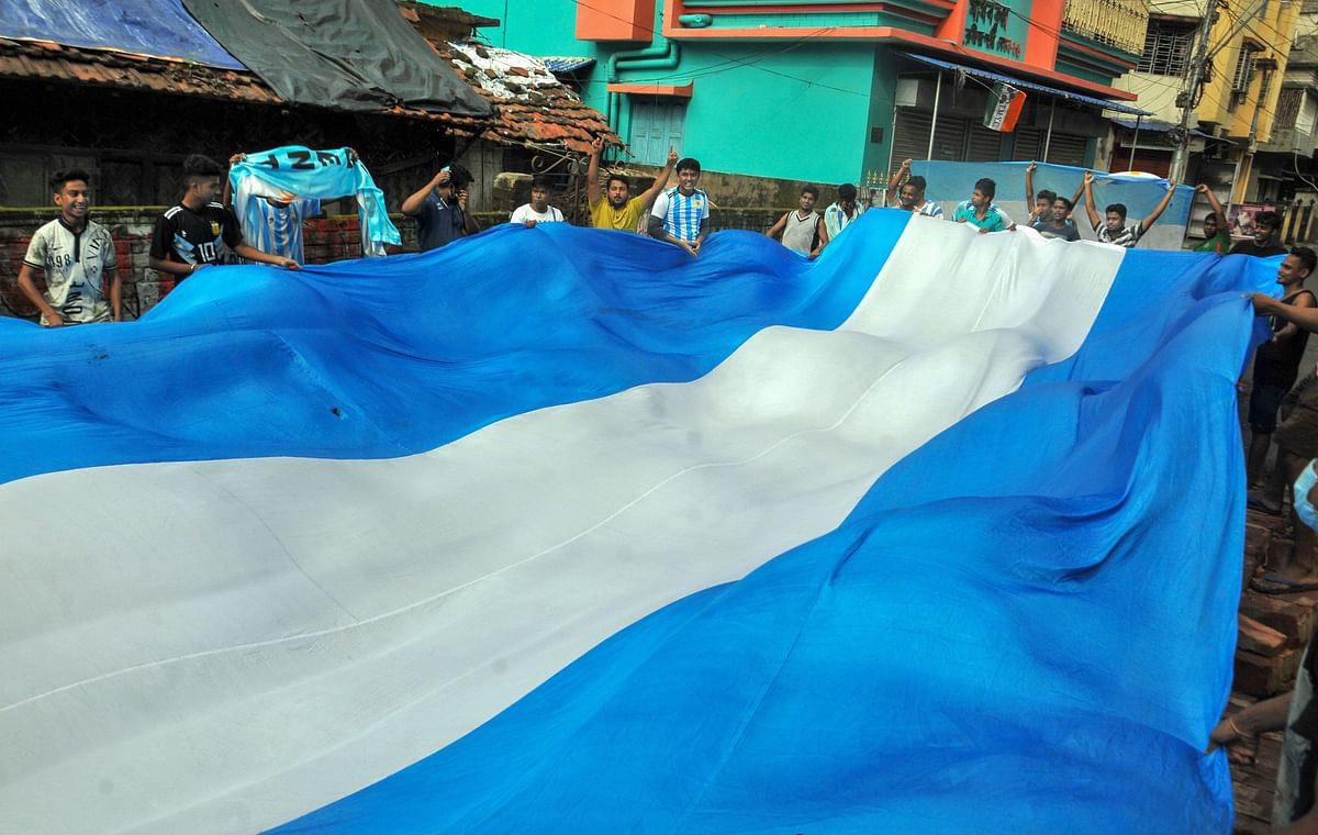 Argentina football fans celebrate with the team flag for their victory over Brazil in the Copa America Soccer final match, in Kolkata, Sunday, July 11, 2021.