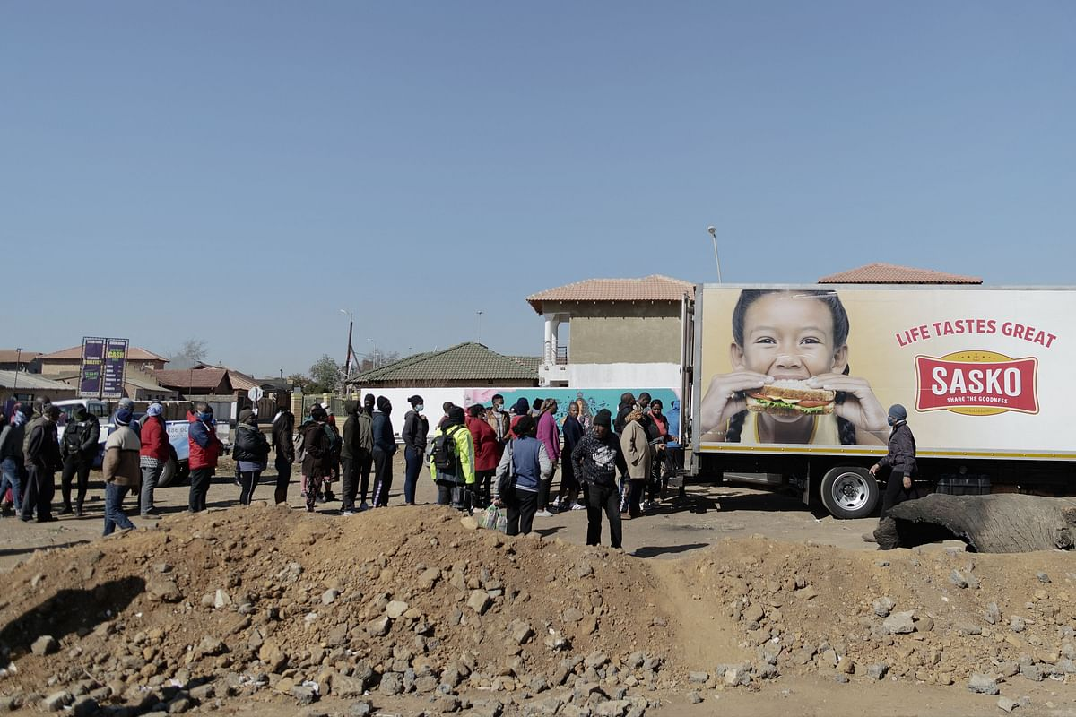 People queue to buy bread from trucks who provide food as shops and mall are looted and closed for business in Soweto, on July 14, 2020.