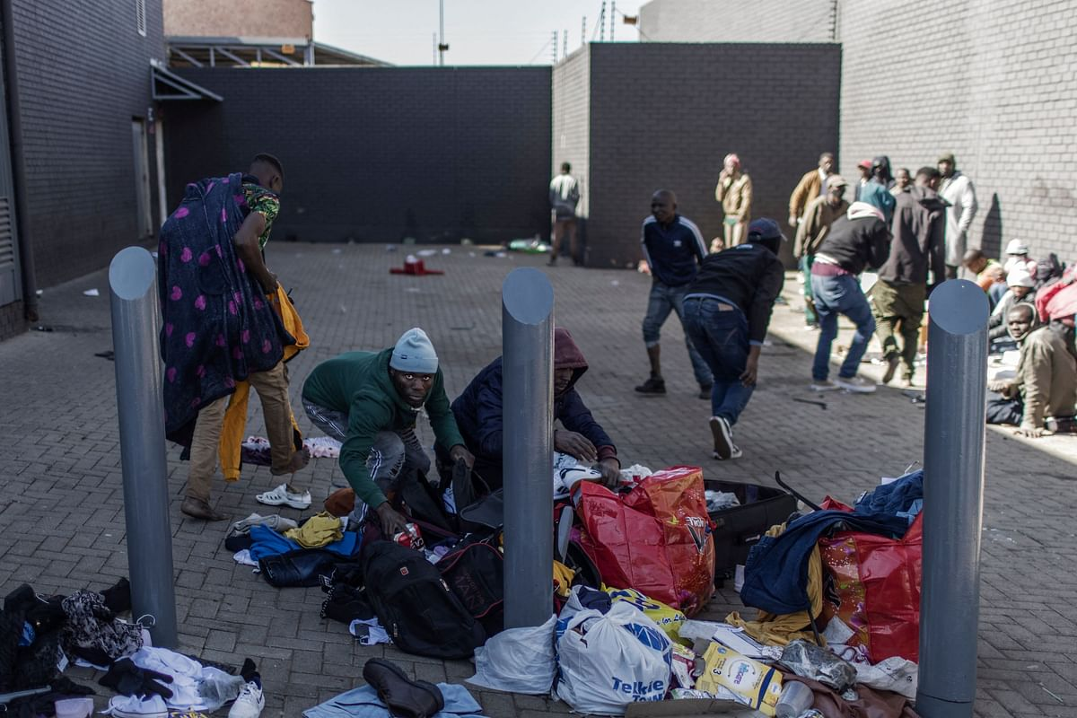A man detaining for looting tries to hide a six-pack of beers in a bag while gathering with other people suspected of looting in a mall in Vosloorus, on July 13, 2021.