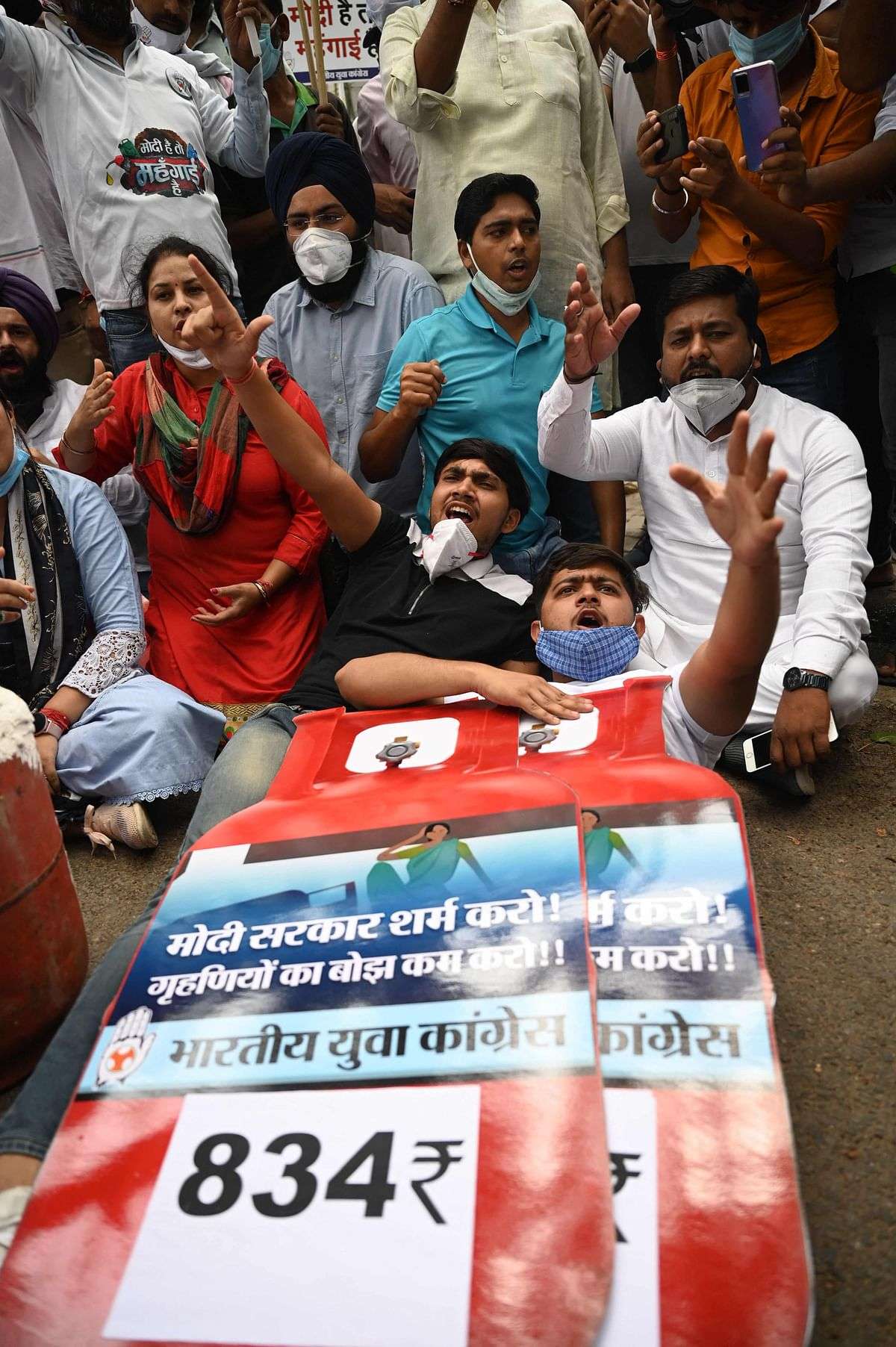 Activists of the Indian Youth Congress (IYC) party hold a large Liquefied Petroleum Gas (LPG) cylinder cutout while shouting slogans during a protest against the recent price hike of fuel and LPG, outside the ministry of petroleum and natural gas in New Delhi on July 3, 2021.