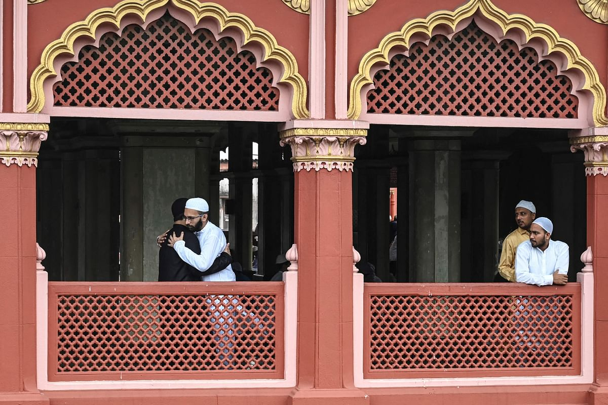 Muslim devotees (L) greet each other after offering prayers during the Eid al-Adha or the Festival of Sacrifice, at Nakhoda Masjid in Kolkata on July 21, 2021.