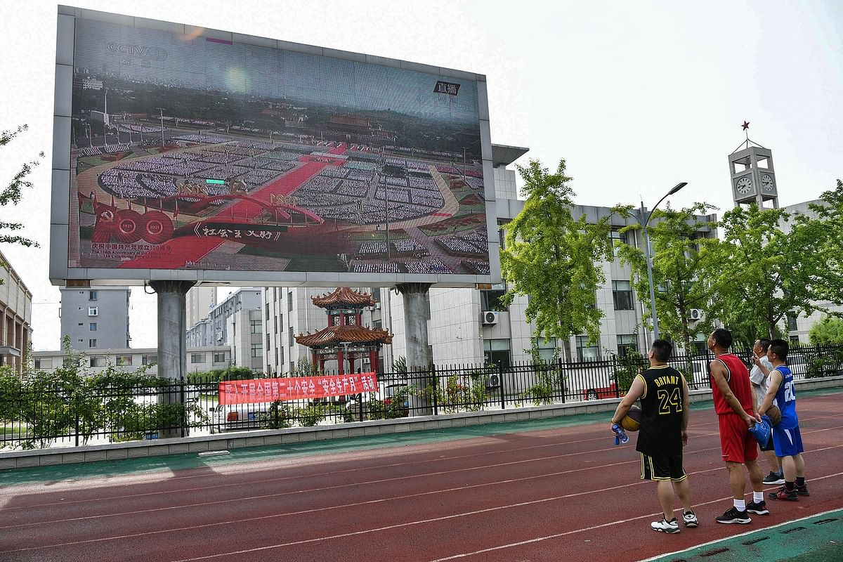People watch a large screen showing the celebrations to mark the 100th anniversary of the founding of the Communist Party of China in Yantai, in Chinas eastern Shandong province on July 1, 2021.