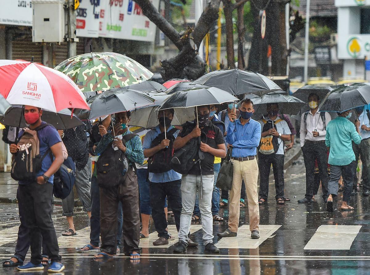 Mumbai: People holding umberllas wait in a queue for a bus during rain at Dadar in Mumbai, Monday, July 19, 2021.