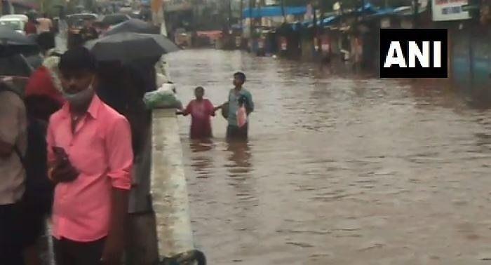 People wade through flooded roads as heavy rains flood Nalasopara