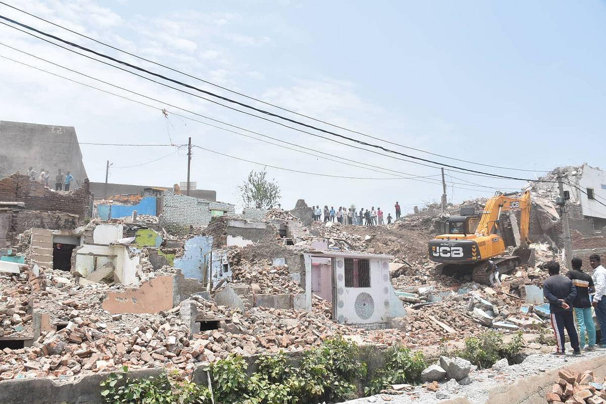 Machines demolish the remains of the homes of Mahakal Tekri area in Ujjain on Sunday