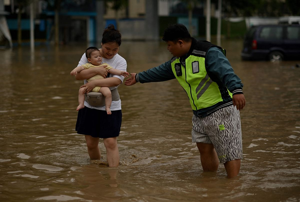 People wade through a flooded street following a heavy rain in Zhengzhou, in Chinas Henan province on July 22, 2021.