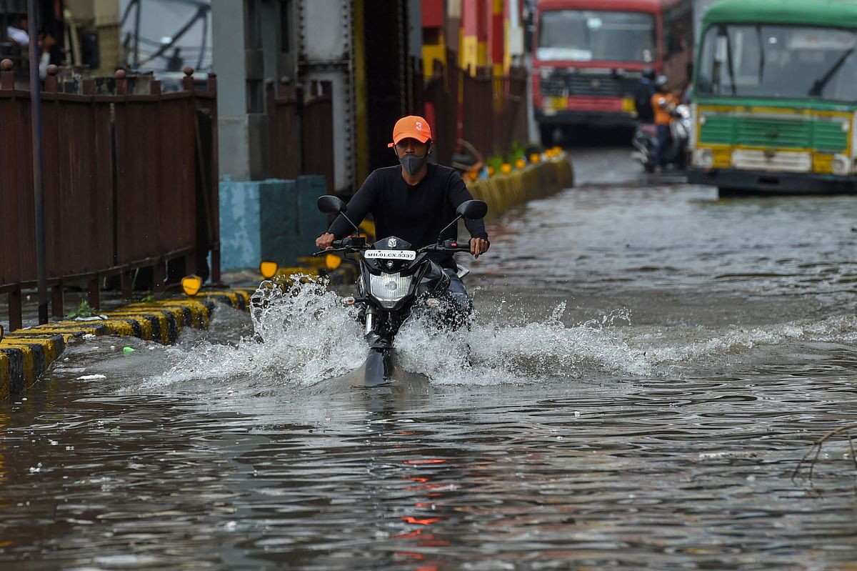 A biker rides through a waterlogged road after a heavy monsoon rainfall in Mumbai on July 16, 2021.