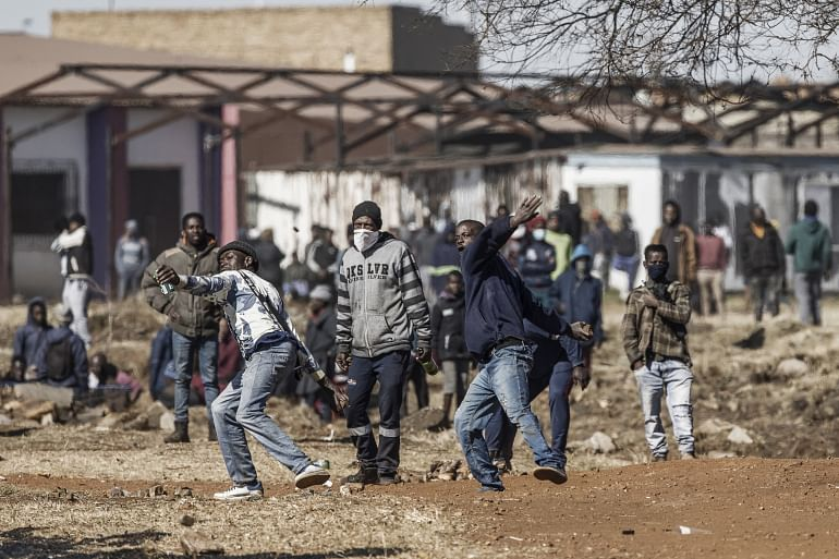 Disgruntled residents throw rocks as they confront police officers at the entrance of a partially looted mall in Vosloorus