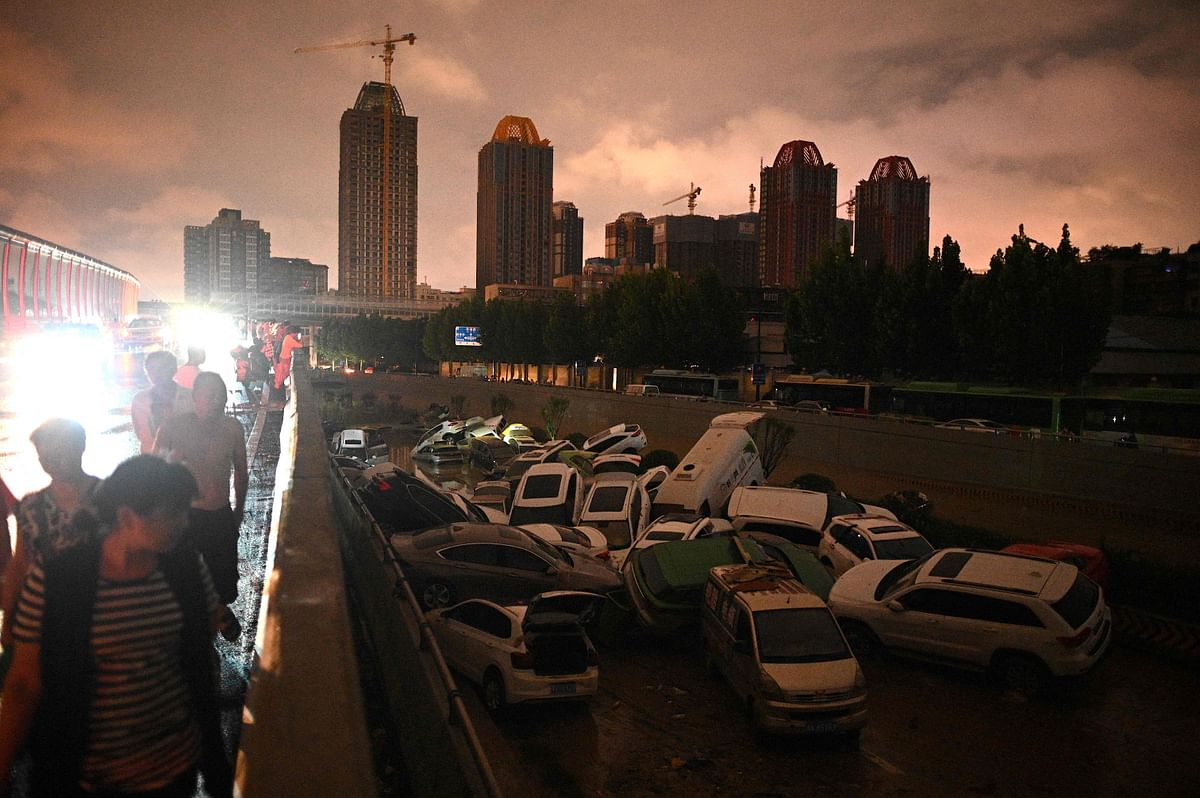 People look at cars stacked on each other at an entrance of a tunnel following a heavy rain in Zhengzhou in Chinas Henan province on July 21, 2021.