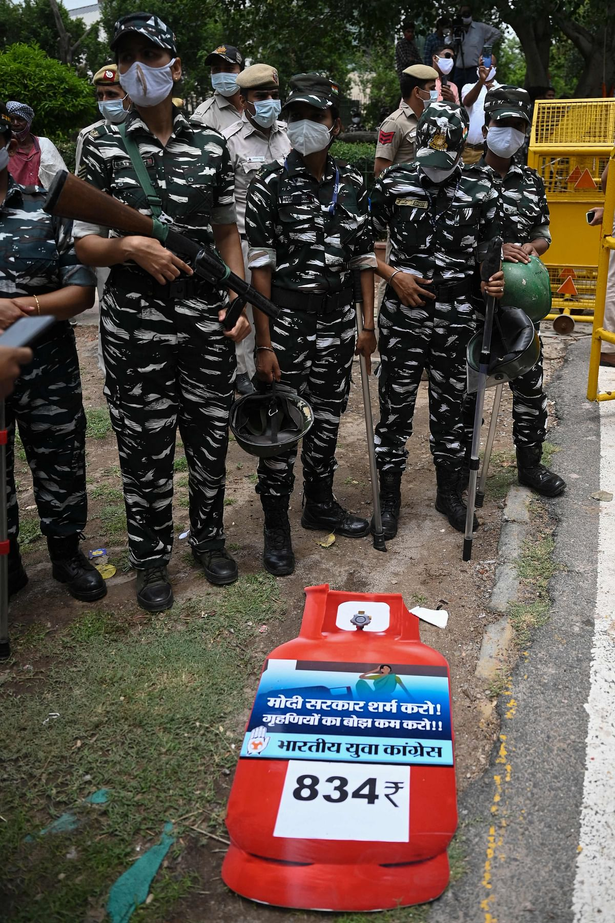 Security personnel stand guard as activists of the Indian Youth Congress (IYC) party (not seen) shout slogans during a protest against the recent price hike of fuel and Liquefied Petroleum Gas (LPG) cylinder, outside the ministry of petroleum and natural gas in New Delhi on July 3, 2021.