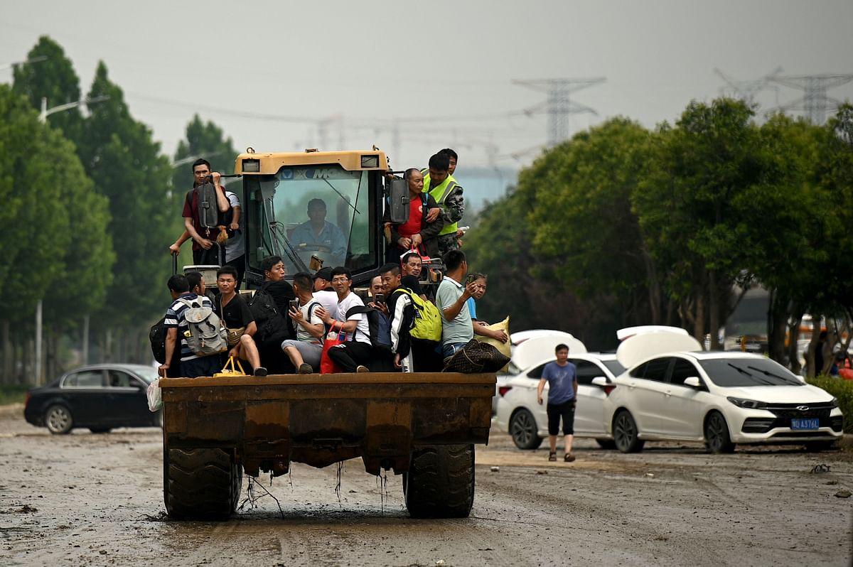 People ride on a bulldozer following a heavy rain in Zhengzhou, in Chinas Henan province on July 22, 2021.