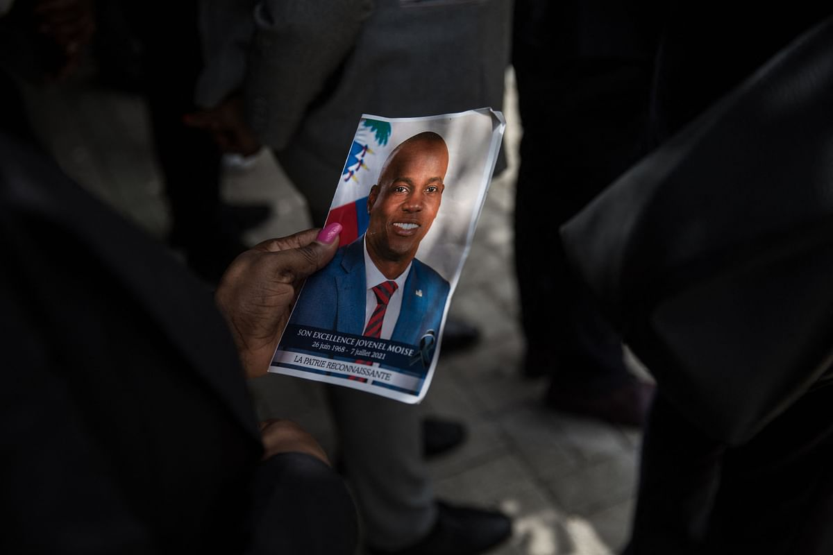 A guest holds a picture of late Haitian President Jovenel Moise during a ceremony at the National Pantheon Museum in Port-au-Prince, Haiti.