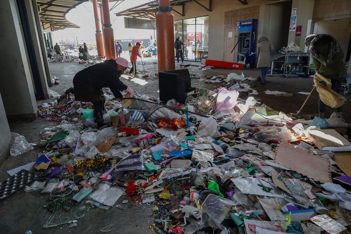 Locals use brooms while volunteering to clean the Diepkloof Square following looting and vandalism in Soweto, Johannesburg on July 14, 2021.