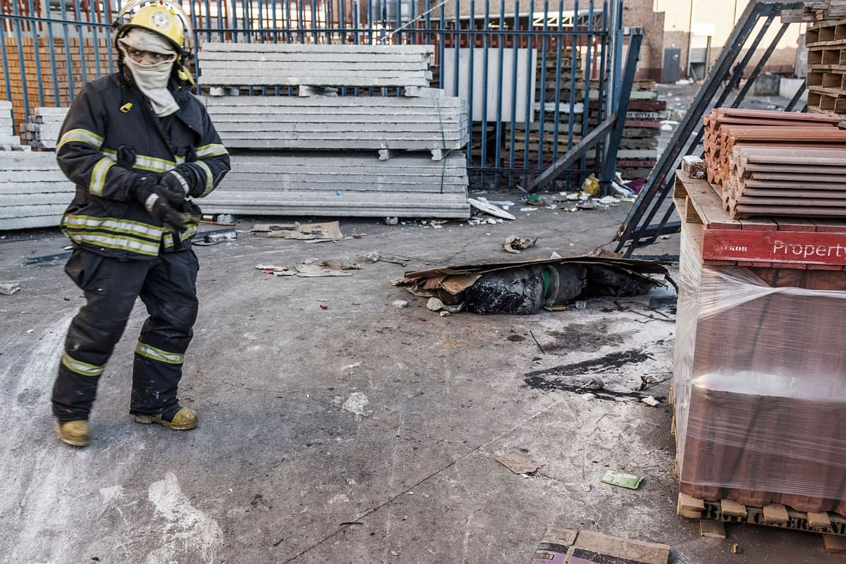 A South African firefighter (L) motions towards the body of a man believed to have been killed overnight at the scene of a looted mall in Vosloorus on the outskirts of Johannesburg on July 14, 2021.