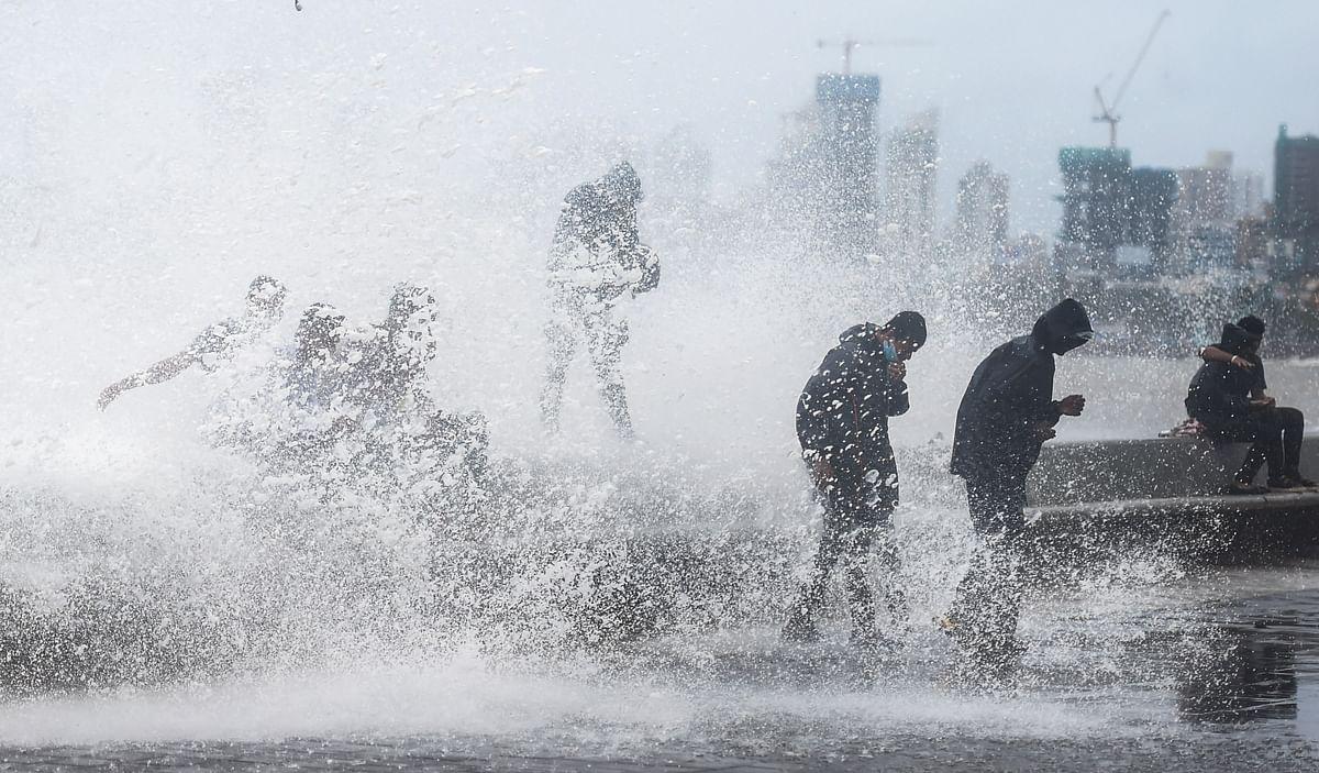 Mumbai: People stand amid crashing waves during high tide at Marine Drive in Mumbai, Monday, July 12, 2021. (PTI Photo/Shashank Parade)