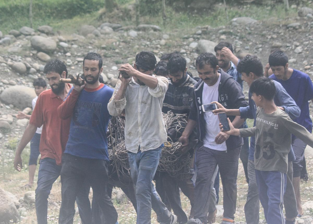 Locals and Wildlife officials carry the tranquilised black bear after it strayed along with its two cubs into northern Kashmir's Baramulla District on July 13, 2021.