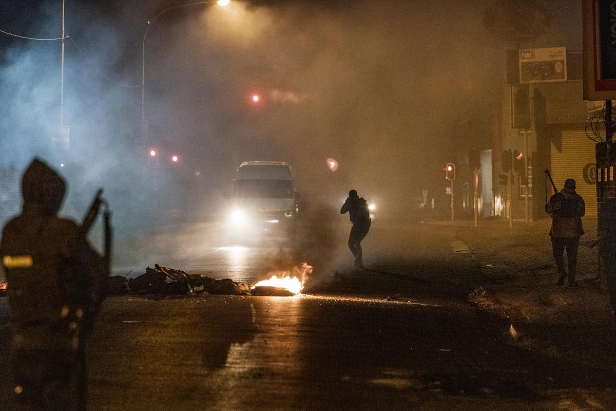 A South Africa Police Service (SAPS) officer aims his rifle at a in incoming minivan bringing it to a stop in Jeppestown, Johannesburg, on July 12, 2021 during clashes with residents of the Wolhuter Mens Hostel.
