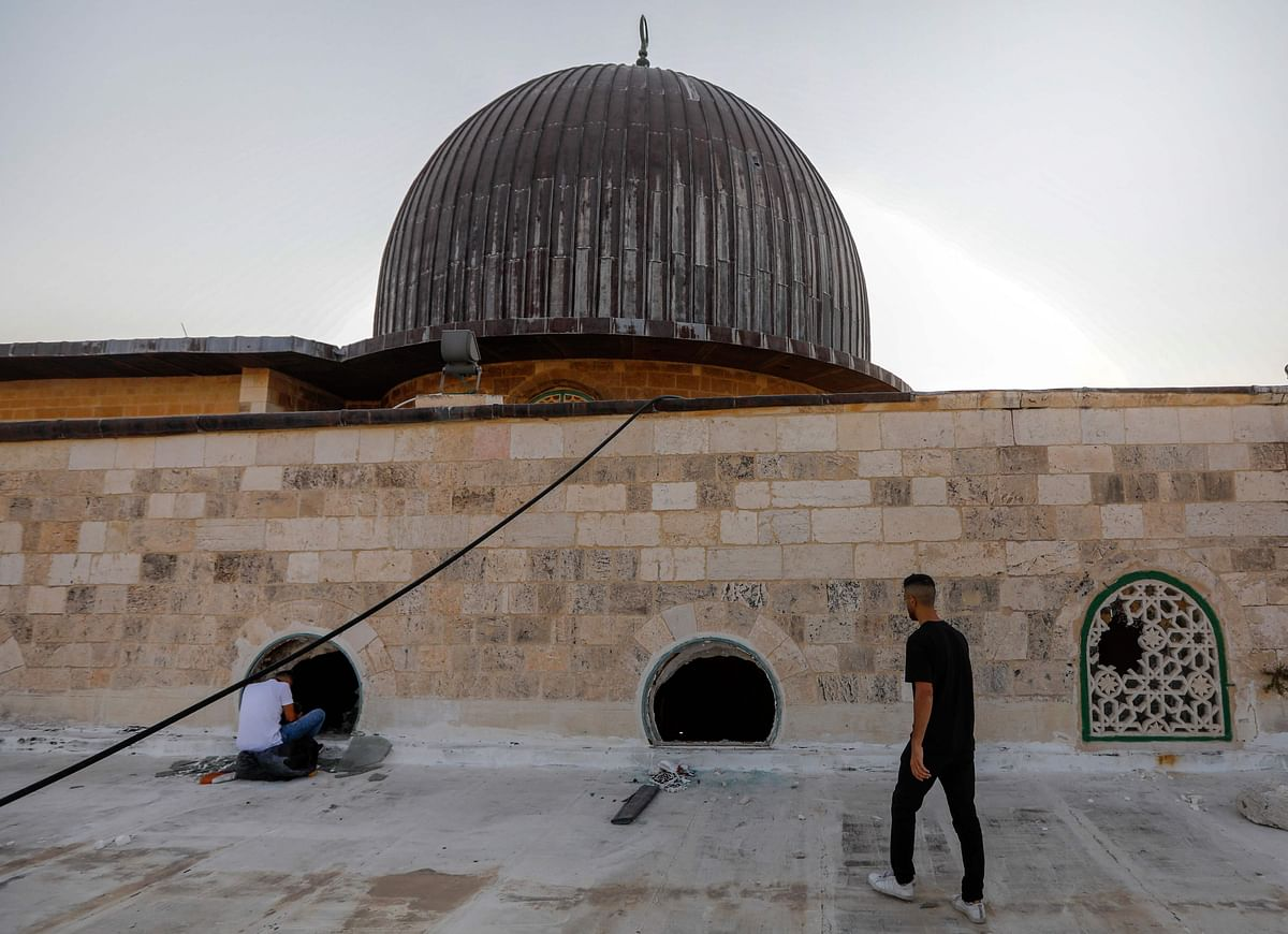 Palestinian youths look into the Al-Aqsa mosque on the first day of the Eid al-Adha feast celebrated by Muslims worldwide, on July 20, 2021, through windows which were shattered two days earlier in renewed clashes between Palestinians and Israeli police at the Al-Aqsa complex in Jerusalems old city.
