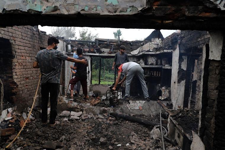 Kashmiri villagers inspect a house damaged in a gunfight in Pulwama, south of Srinagar