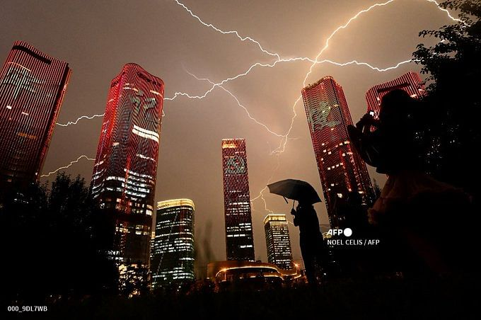 People look at buildings displaying a light show on the eve of the 100th anniversary of the Chinese Communist Party in Beijing on July 1, 2021.