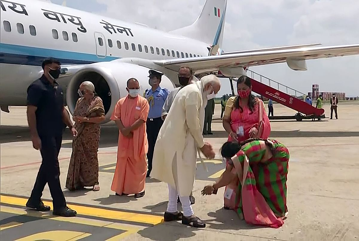 A woman touches the feet of Prime Minister Narendra Modi as he arrives at the airport, in Varanasi on Thursday. UP CM Yogi Adityanath and Governor Anandiben Patel were also present.