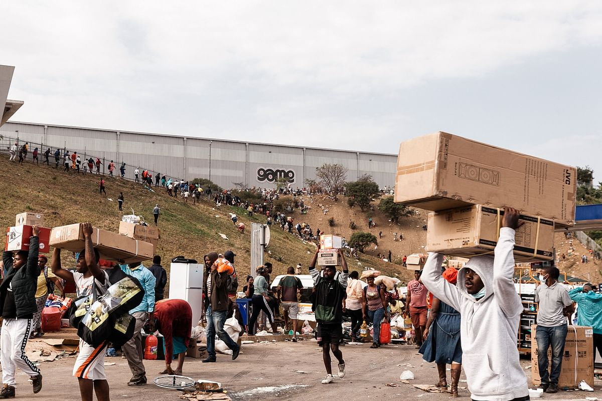 Suspected looters carry goods from the Game Warehouse in Durban on July 13, 2021.