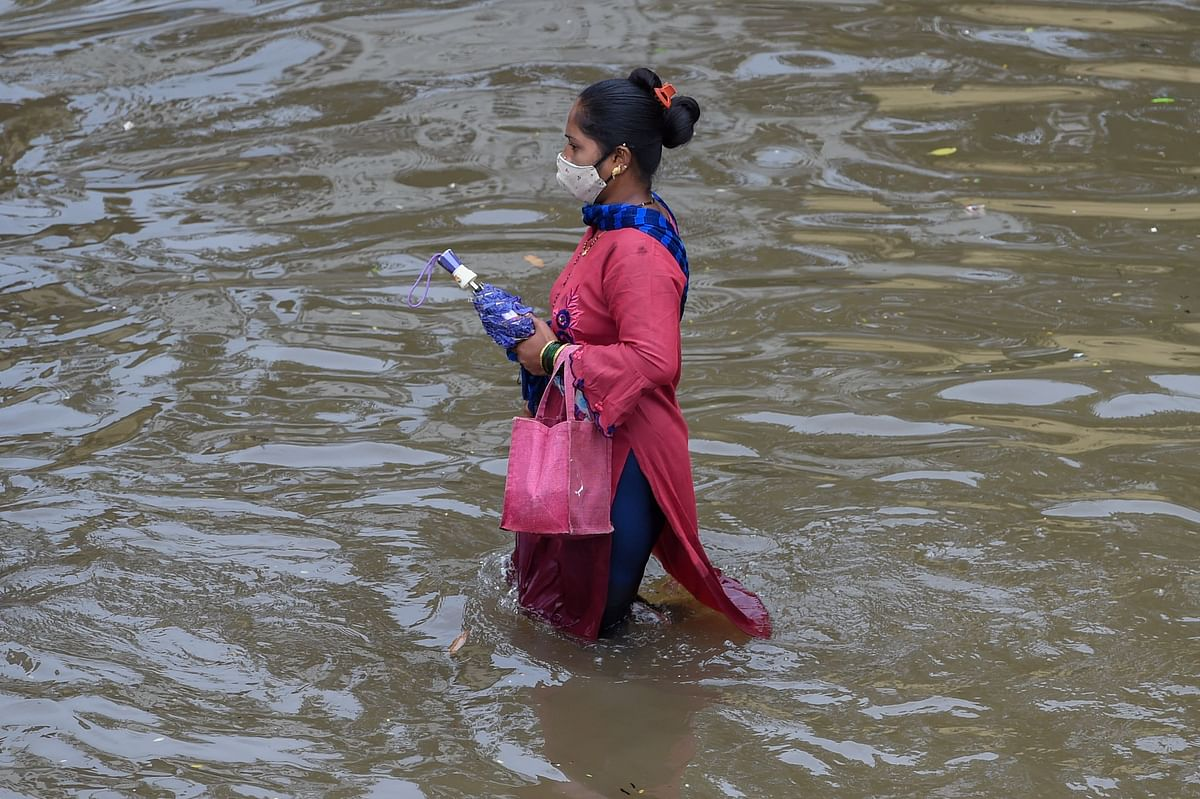 A woman wades through a waterlogged road after a heavy monsoon rainfall in Mumbai on July 16, 2021.