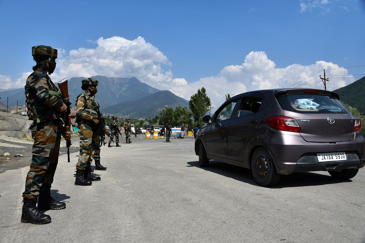 The soldiers stand on guard alongside passing vehicle