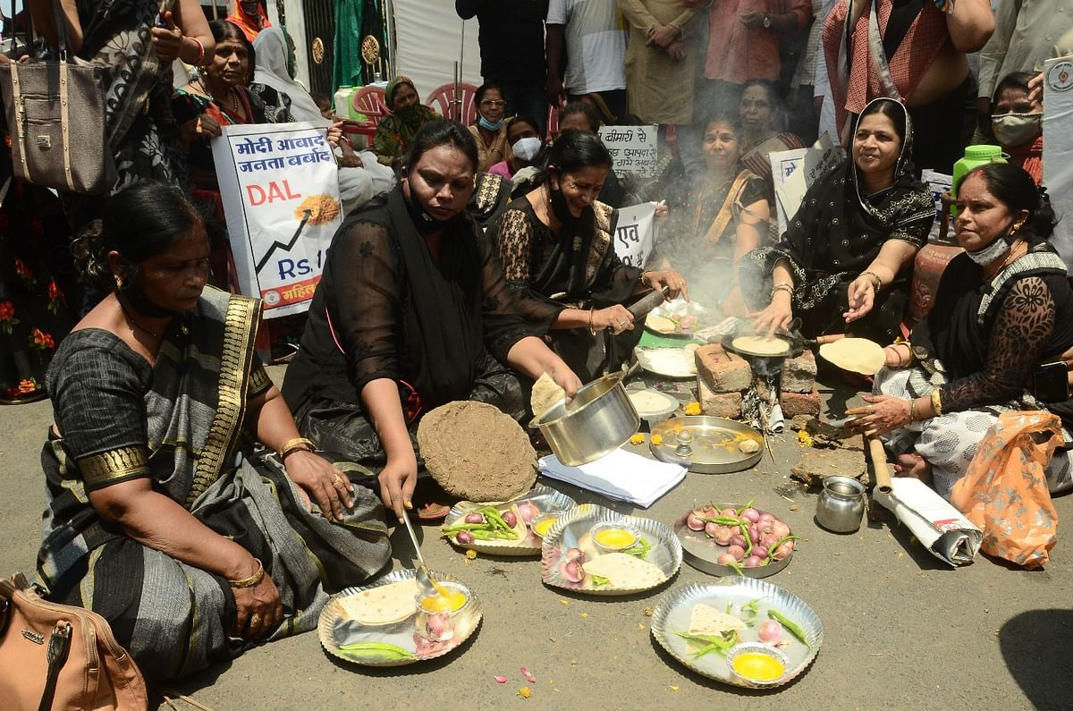 Women Congress workers prepare lunch on a stove, near Tower Chowk. They staged a protest against steep hike in the prices of diesel-petrol and LPG cylinders