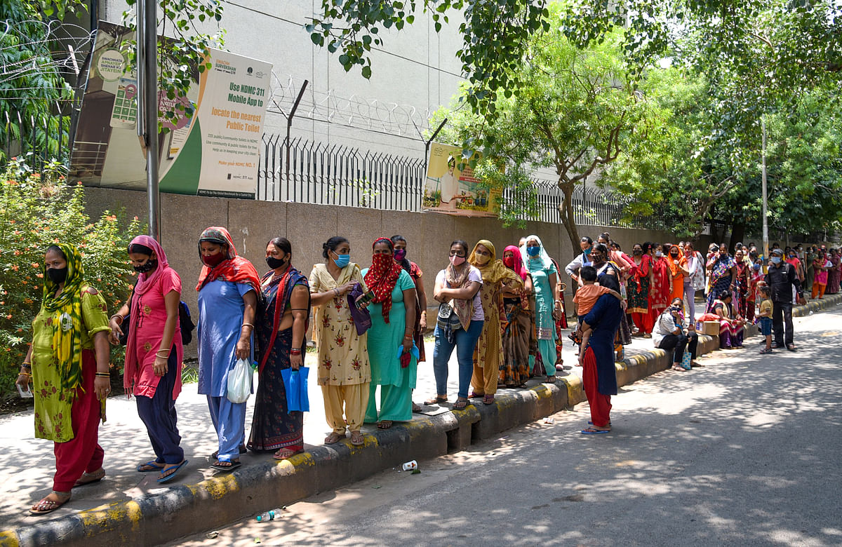 New Delhi, July 10 (ANI): People stand in a queue to get a dose of COVID-19 vaccine during a free vaccination drive for the underprivileged, at the Navyug school near Sarojini Nagar Market, in New Delhi on Saturday.