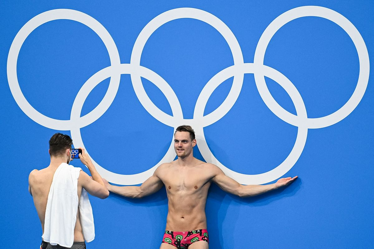 Athletes pose in front of the Olympic ring