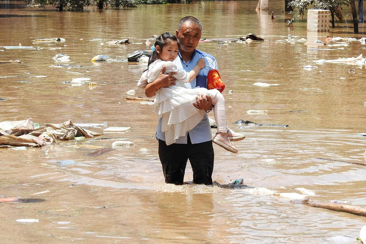 This photo taken on July 12, 2021 shows a village official evacuating a child from a flooded area following heavy rains in Dazhou in Chinas southwestern Sichuan province.
