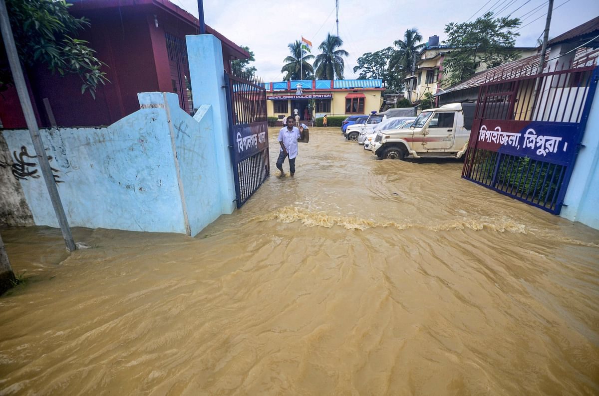 A villager wades through a flooded street after heavy rain in Bishalghar village on the outskirts of Agartala, Thursday, July 1, 2021.